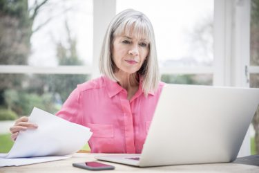 Senior woman concentrating on laptop with paper documents in hand. Senior woman working at home with computer.